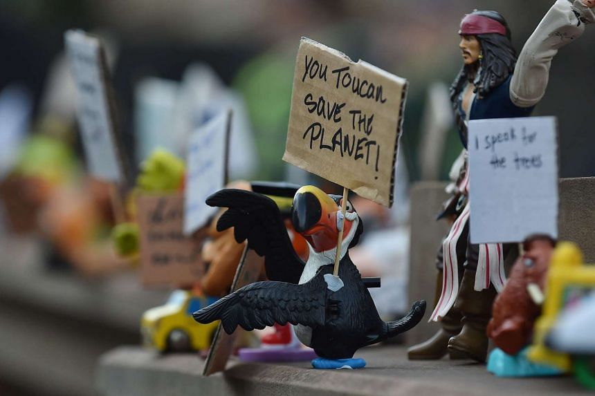 Figurines holding small signs are displayed during a climate change rally.