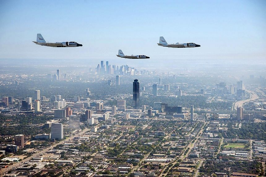 A Nasa handout shows the last three airworthy WB-57 aircraft photographed from a Navy T-6 aircraft while flying in formation over Houston, Texas, and the Johnson Space Centre last week for a historic photo flight. The WB-57s have been flying high-alt