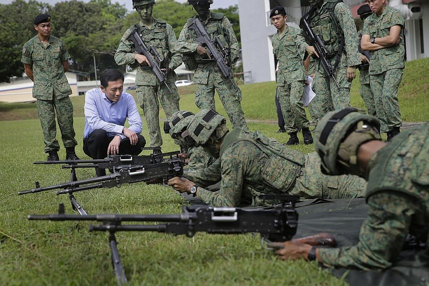 (Far left) Senior Minister of State for Defence Ong Ye Kung watching soldiers at the Amoy Quee Camp executing simulation drills that tested how quickly they can get ready for a mock invasion. (Left) Soldiers responding with a rousing cry as their com