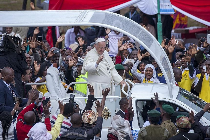 Pope Francis waving to the crowd at the University of Nairobi in Kenya, as he arrived yesterday to conduct an open-air mass for tens of thousands of people. Bridging divisions between Muslims and Christians is a main theme of the Pope's first tour of