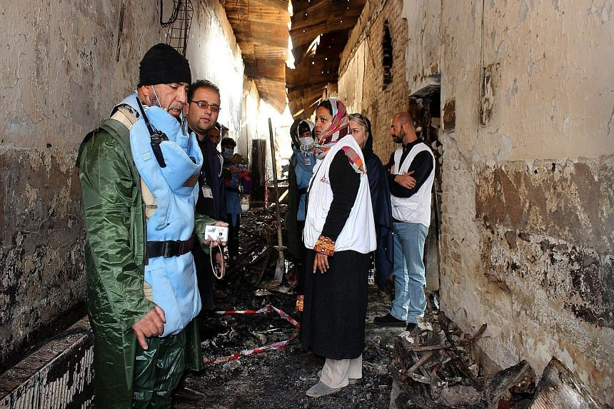 An Afghan worker (left) with staff of the Doctors Without Borders hospital in northern Kunduz that was attacked in error by US forces. The air strike was supposed to hit a nearby Taleban-held compound.