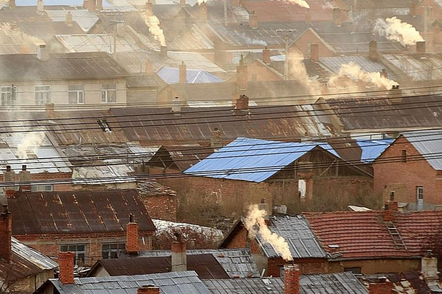 Chimneys of houses in Heihe, in north-eastern China's Heilongjiang province, spewing smoke. China, the US and the EU - some of the biggest emitters - have pledged contributions towards reducing greenhouse gas emissions, as have many other countries.