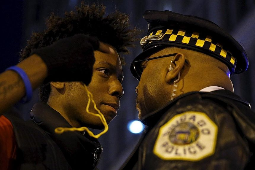 A protester in a face-off with a police officer during a demonstration in Chicago, Illinois, on Wednesday, in response to the fatal shooting of Laquan McDonald. The authorities in Chicago had girded for the possibility of civil unrest over a newly is