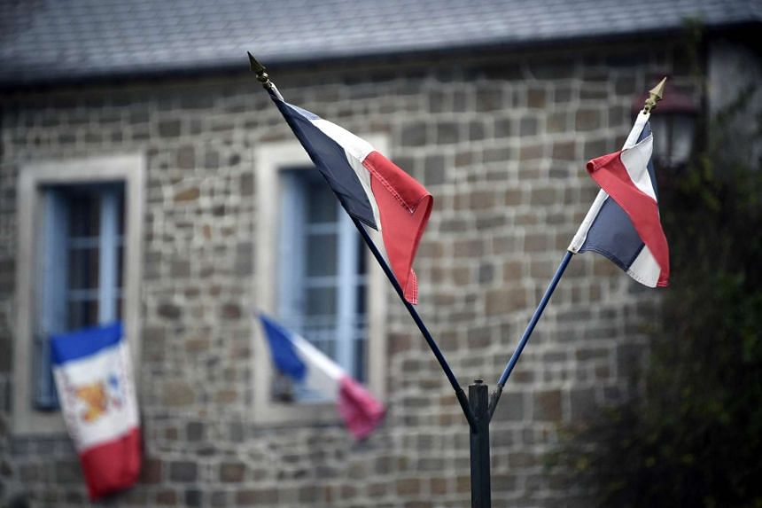 French national flags put on a window during the remembrance ceremony on Nov 27, 2015.