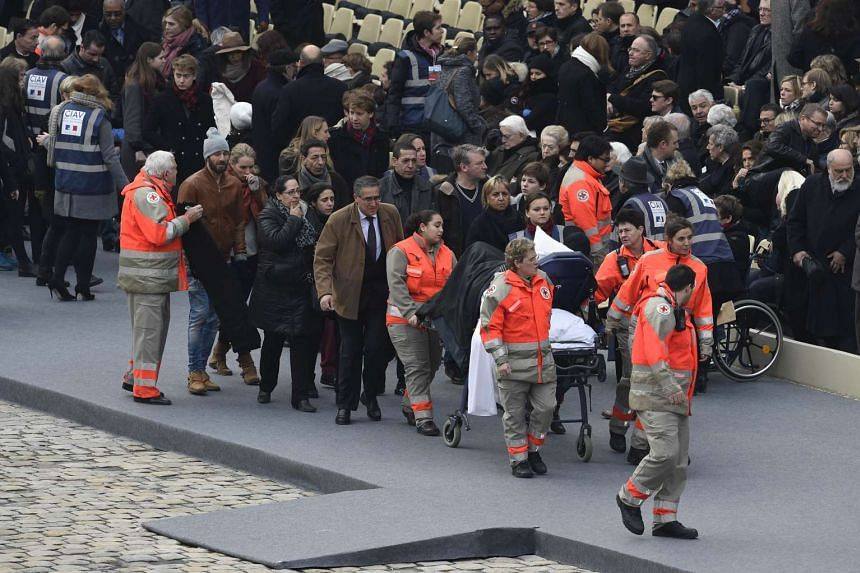 Members of the French Red Cross accompany people wounded in the Paris terror attacks during the remembrance ceremony on Nov 27, 2015.