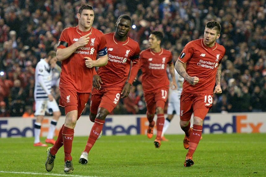 Liverpool's English midfielder James Milner (left) celebrates after scoring from the penalty spot.