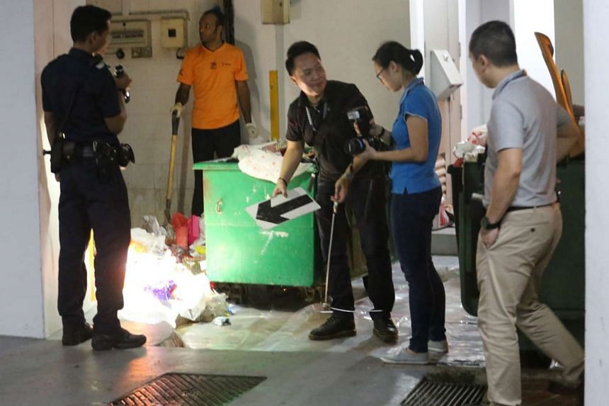 Investigators inspecting the scene of the stabbing at Boon Lay Drive.