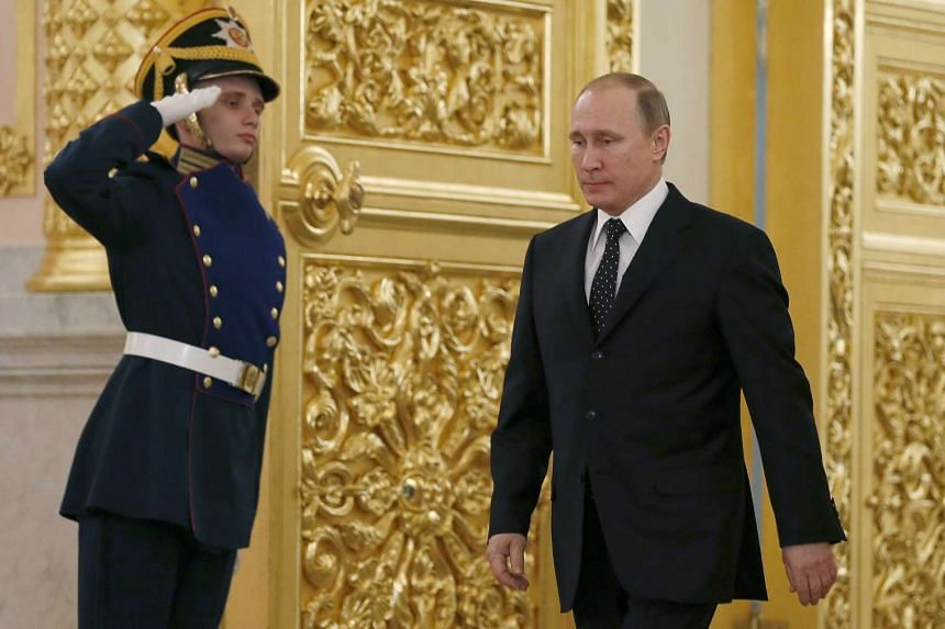 Putin walks past an honour guard as he attends a diplomatic ceremony at the Kremlin in Moscow.