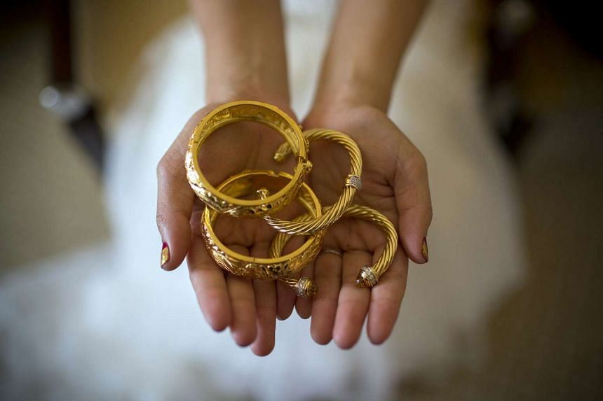 A bride holding gold bangles for a photograph during her wedding in Hong Kong in 2014.
