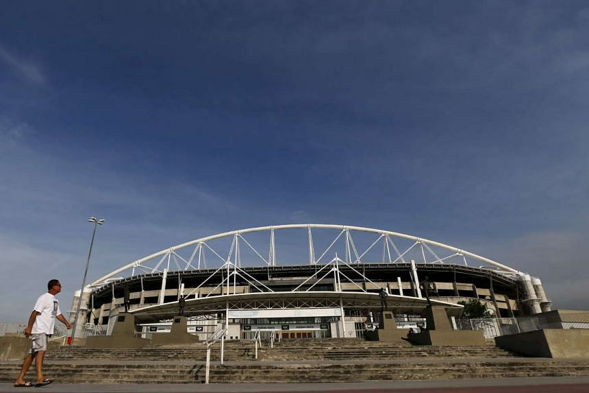 A man walks in front of the Olympic Stadium, undergoing renovation to stage athletic competitions during the Rio 2016 Olympic Games, in Rio de Janeiro, Brazil, on Nov 9, 2015.