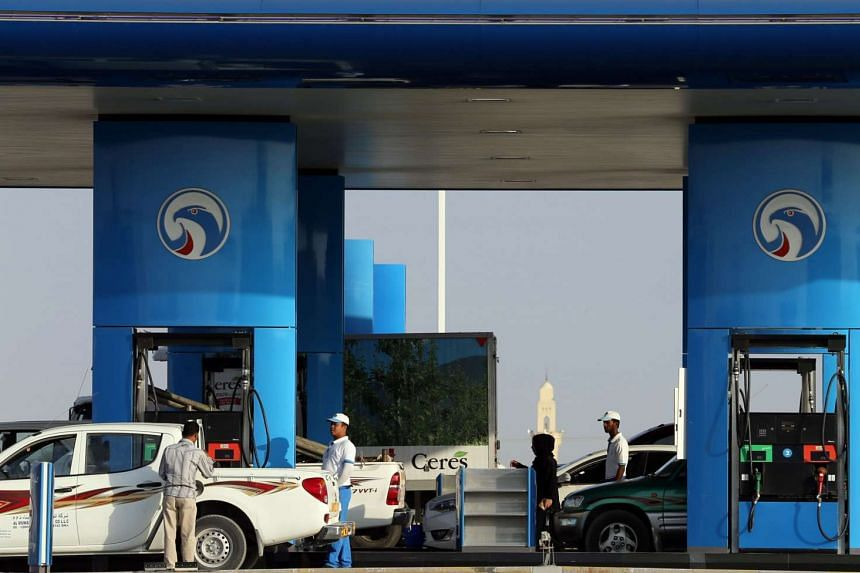 Workers filling cars with petrol at a station in Dubai on Nov 24.