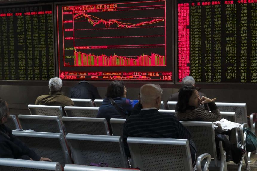 Investors monitor stock market data at a securities brokerage house in Beijing, China.