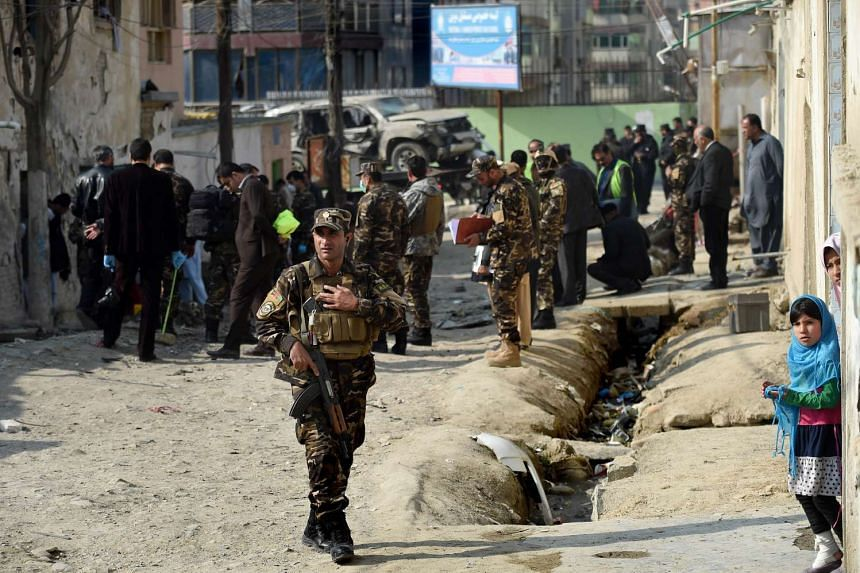 Afghan security forces inspect the scene of a suicide bomb attack at Kart-e-Naw in Kabul on Nov 28, 2015.