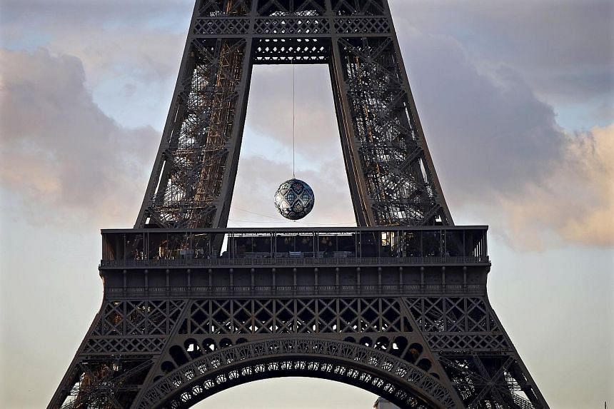 Artwork Earth Crisis by American artist Shepard Fairey is suspended at the Eiffel Tower in Paris, France. The capital will host the World Climate Change Conference 2015 from Nov 30 to Dec 11.