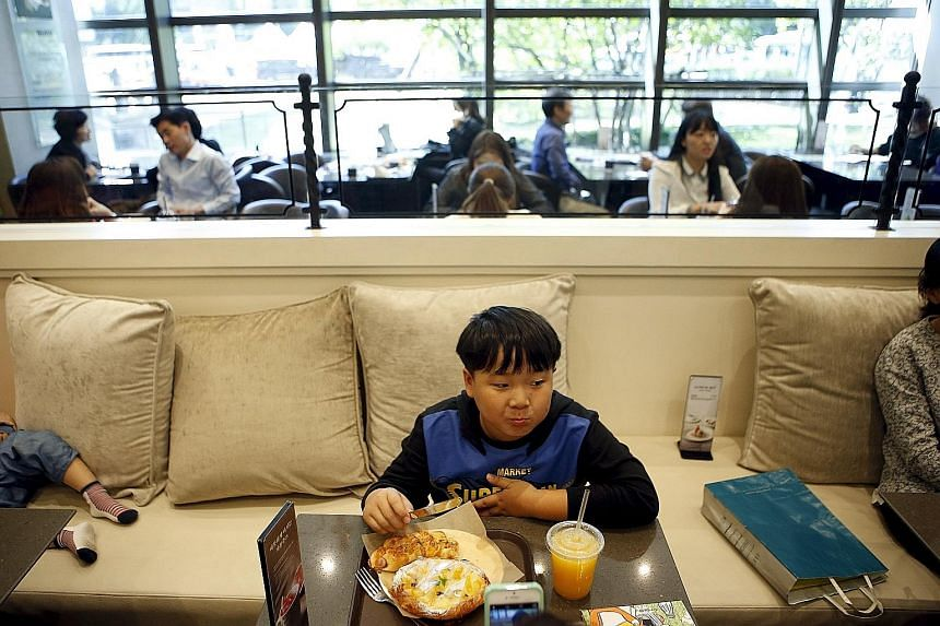 A boy eating bread at an eatery in Seoul. The nation's per capita flour consumption registered a high of 33.6kg last year - slightly over half of the 65.1kg for rice.