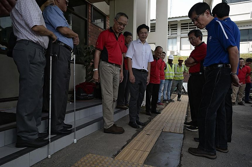 National Development Minister Lawrence Wong (centre, white shirt) and BCA chief executive John Keung (third from right, in red) checking out the newly installed tactile ground panels at the SAVH compound yesterday.