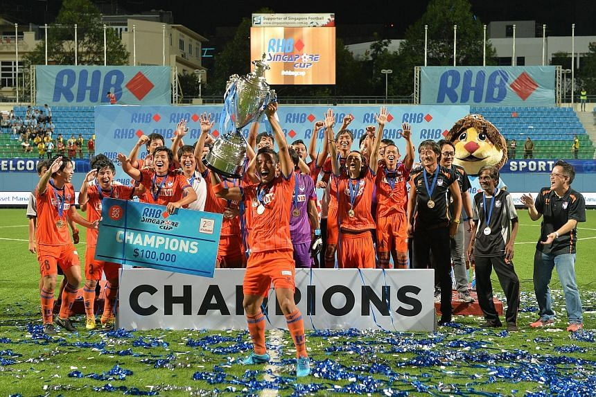 Albirex captain Yosuke Nozawa hoisting the RHB Singapore Cup as players and staff celebrate on the Jalan Besar Stadium pitch. The Japanese side finished third in the S-League, equalling their best result.
