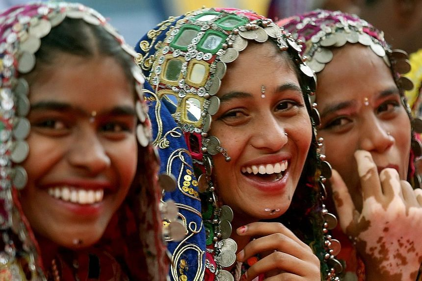 Indian school girls wearing tribal costumes at a Children's Day celebration in Bangalore. New discoveries point to fresh ways of thinking about happiness.