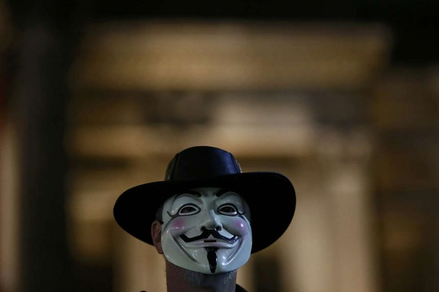 An Anonymous supporter wearing the mask associated with the hacker group.
