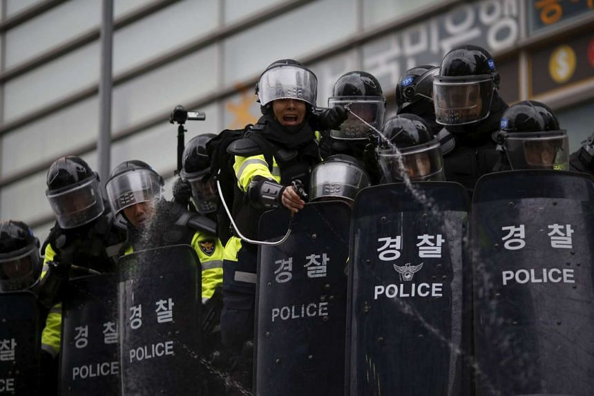 Riot policemen using pepper spray to disperse protesters during an anti-government rally in central Seoul, South Korea, on Nov 14, 2015.