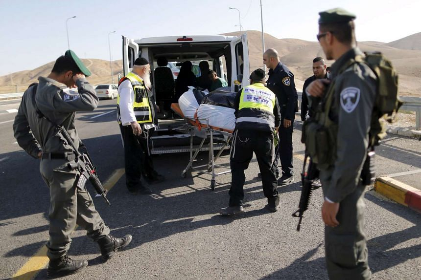 The body of a Palestinian who is said to have rammed his vehicle into Israeli soldiers is taken away.