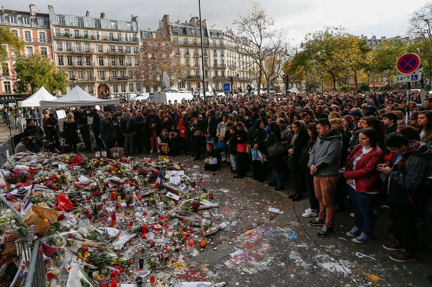 Thousands of people observe a minute of silence near the Bataclan concert venue after the attacks in Paris.