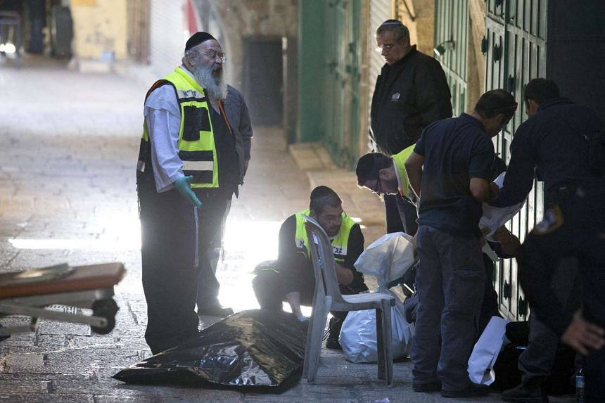 Members of an Israeli community emergency response team working at the site where a Palestinian man was killed after he stabbed an Israeli police officer, on Nov 29, 2015.
