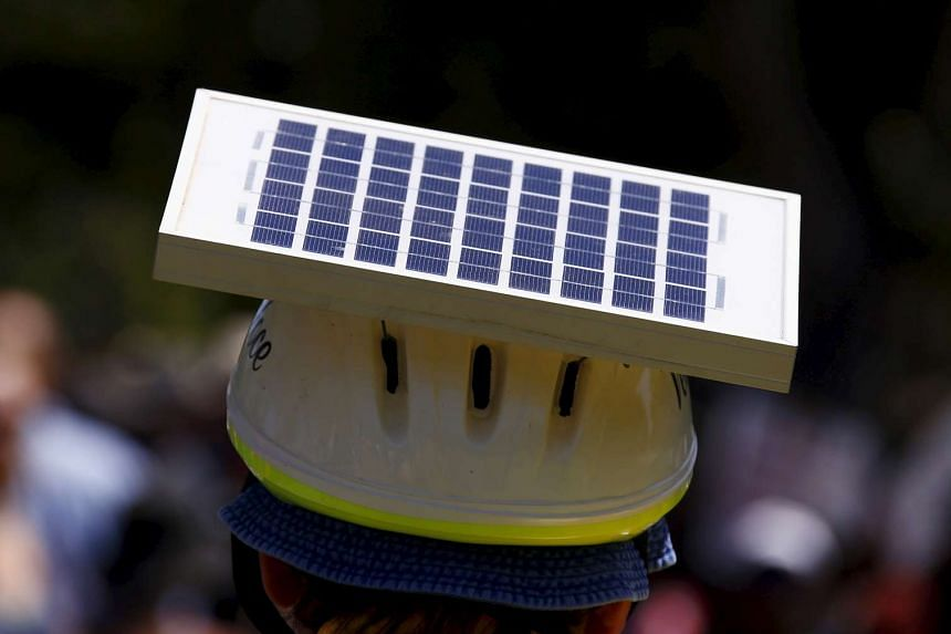 A cyclist wears a helmet with a solar panel attached as he participates in a march the day before the Paris World Climate Change Conference, along the main street of Adelaide, South Australia.