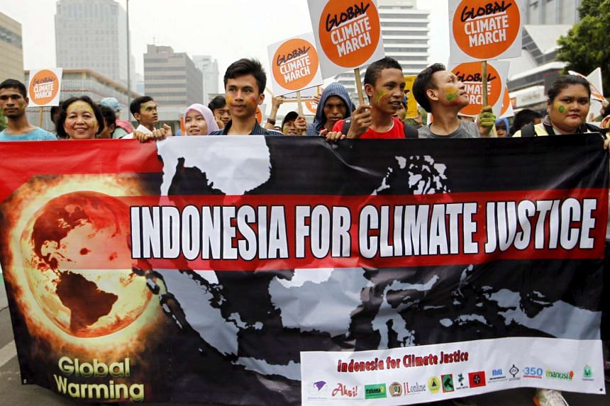 People hold placards and banners as they participate in a march ahead of the Paris World Climate Change Conference in Jakarta on Nov 29, 2015.
