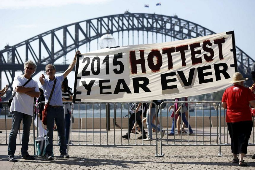 Protesters hold a banner in front of the Sydney Harbour Bridge during a rally ahead of the UN climate change summit in Paris on Nov 29, 2015. More than 2,000 climate events are planned in cities including Sydney, Jakarta, Berlin, London, Sao Paulo an