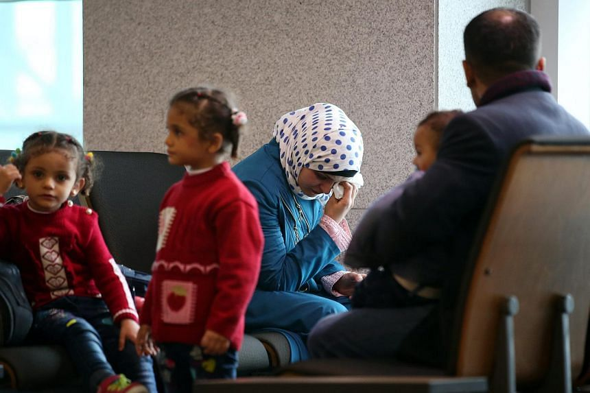 A woman who identified herself as a Syrian refugee tears while waiting at the immigration office of Incheon International Airport, South Korea, on Nov 18, 2015, with people who appear to be her family.