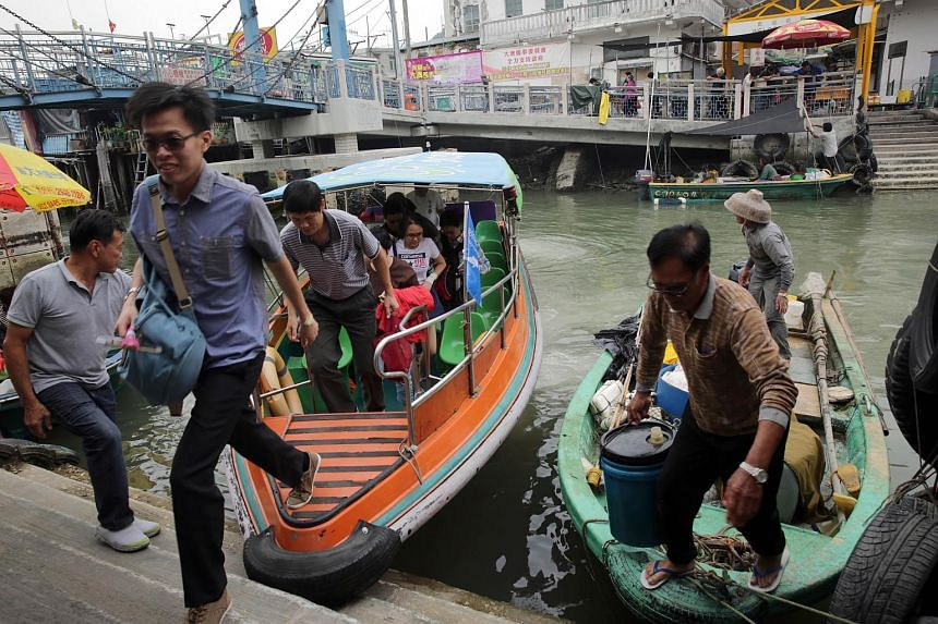 Customers (left) getting off a tour boat after a trip to see the famous pink dolphins in the waters around Tai O in Hong Kong.