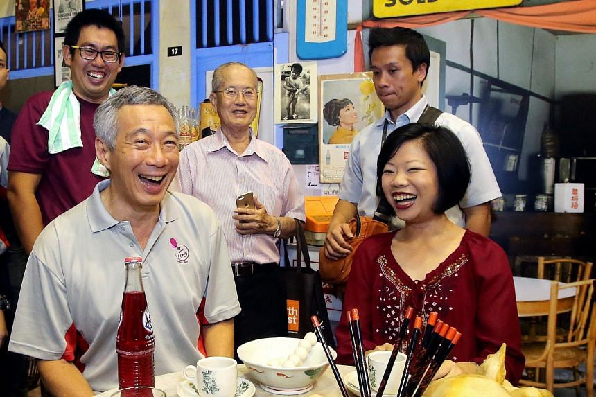 PM Lee and Ms Sim at the carnival yesterday to mark the constituency's 60th anniversary. Three books celebrating the area's heritage, and the Bukit Timah Eldercare Project were launched at the event.