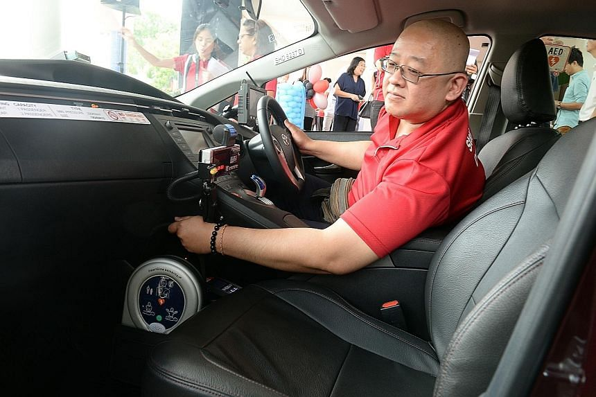 Cabby Simon Ngiam with the automated external defibrillator in his taxi. About 120 SMRT cabbies have volunteered for this initiative.
