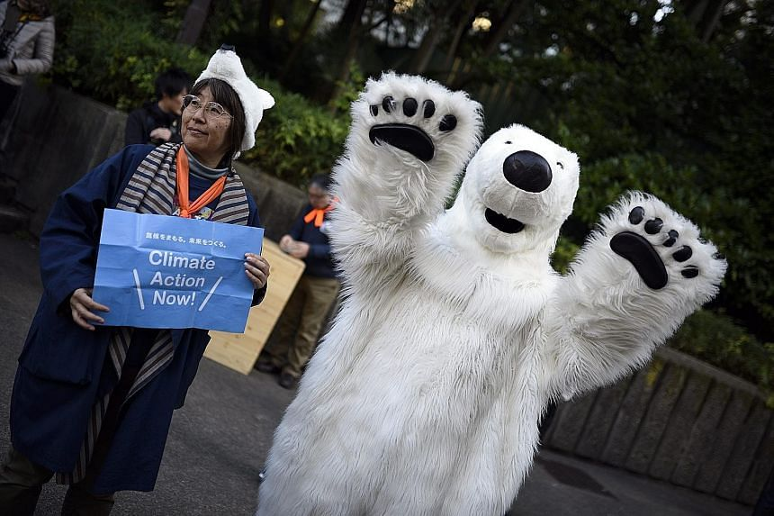 A person in a polar bear costume at the Earth Parade event in Tokyo, Japan, yesterday. The task of the Paris talks is to reach the first truly universal climate pact that binds 195 nations to new emission limits from 2020.