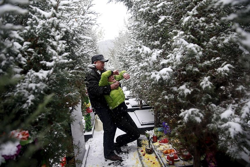 Mr Fan Guohui comforting his wife, Madam Zheng Qing, as they show their son's resting place to reporters on their visit to the graveyard in Zhangjiakou, China, last Sunday. Madam Zheng Qing hugging her dead son's favourite jacket during an interview