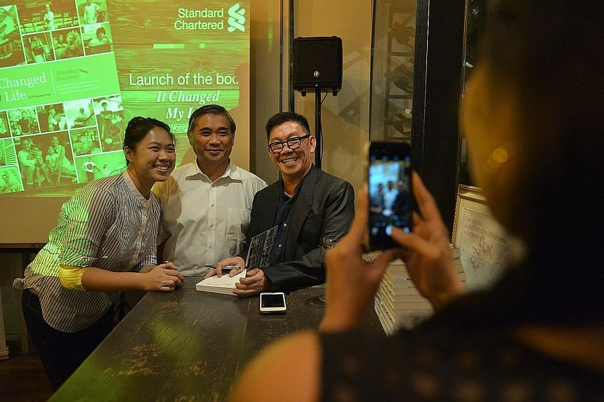 Mr Wong Kim Hoh (right) with one of his interviewees, Mr Toh Chin Siong, a used furniture salesman, and his daughter Brillyn at the launch of It Changed My Life at The Straits Wine Company, UE Square, last week. The book is a collection of 39 stories