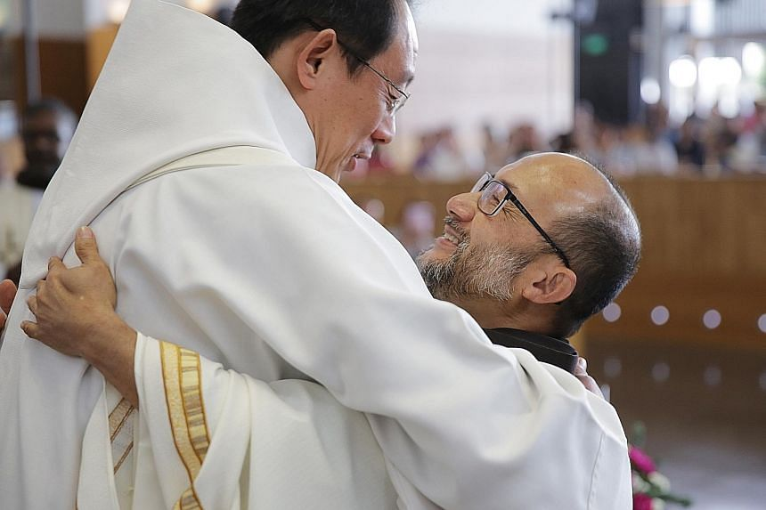 Above: Father Rowland Yeo, 58, (right) hugging Father John-Paul Tan, Order of Friars Minor, Chancellor (Chancery of the Roman Catholic Archdiocese of Singapore), after he was ordained a priest yesterday. Left: Father Yeo built tables and chairs in hi
