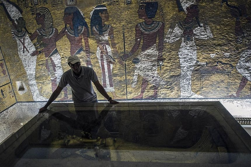 """An archaeologist with the sarcophagus of King Tutankhamun in his mausoleum. """"We are saying now it's 90 per cent likely there is something behind the walls,"""" said Egypt's antiquities minister."""