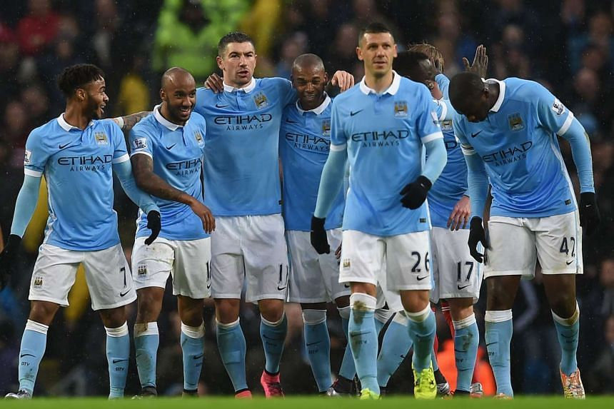 Manchester City's English midfielder Fabian Delph (second left) celebrates with teammates after scoring.