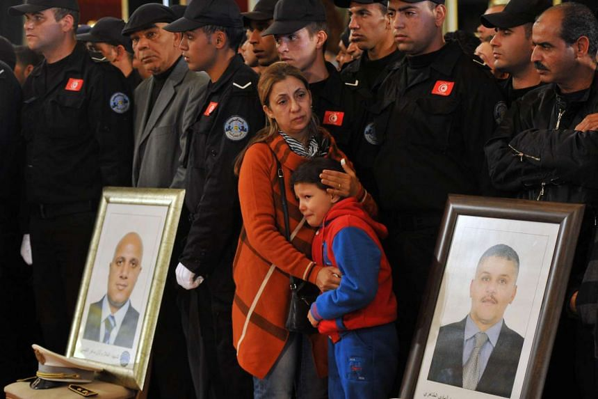 Family members of the presidential guards who were killed mourn them at a remembrance ceremony.