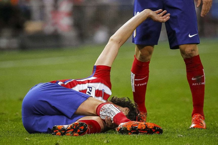Atletico Madrid's Portuguese midfielder Tiago Mendes reacts after being injured.