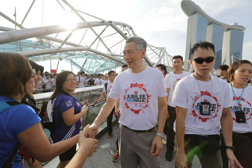 PM Lee (third from left) shook hands with others and exchanged high fives with young children.