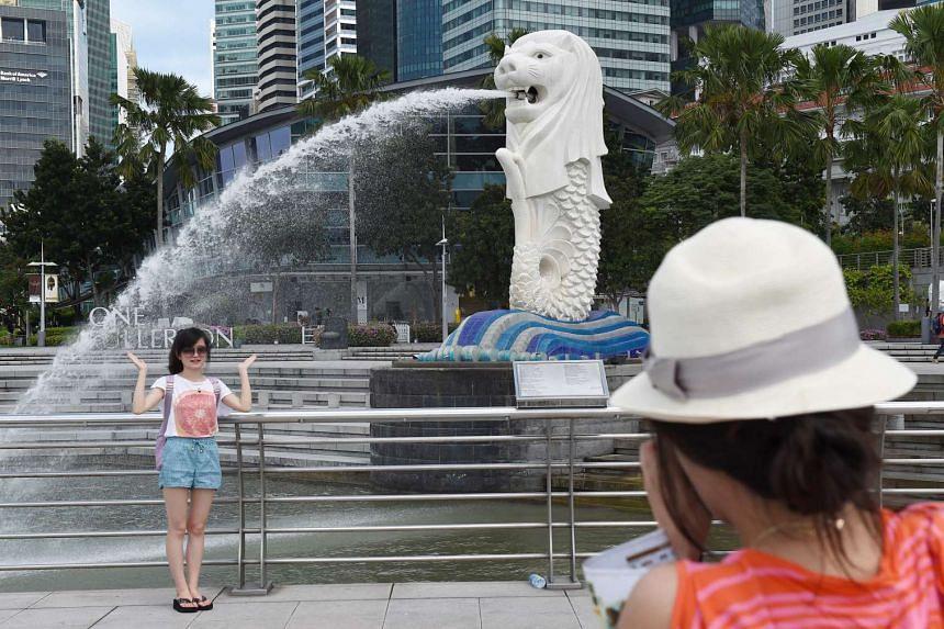Tourists taking photos next to the Merlion.
