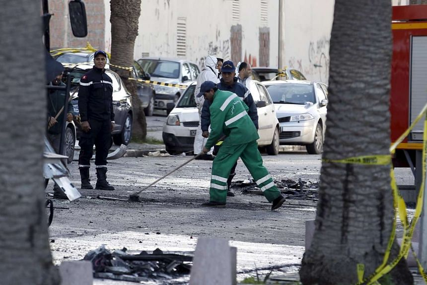 A sanitary service worker cleaning up at the scene of a suicide bomb attack in Tunisia.