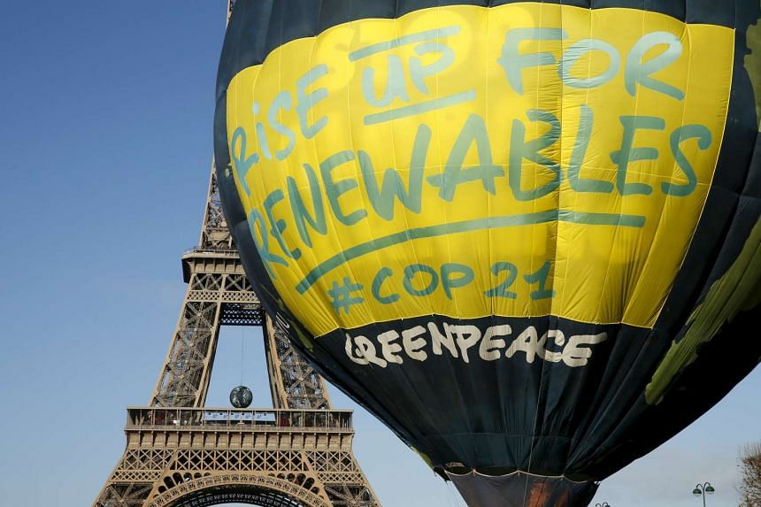 Greenpeace activists fly a hot air balloon next to the Eiffel tower ahead of the 2015 Paris Climate Conference.