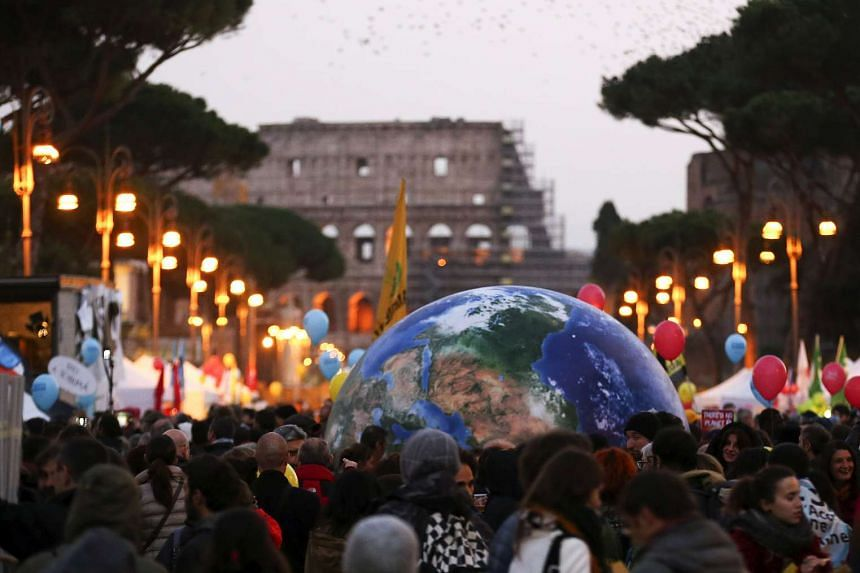 Protesters carry a globe-shaped balloon in front of Rome's Colosseum during a rally held the day before the start of the 2015 Paris Climate Change Conference in Rome, Italy, Nov 29, 2015.