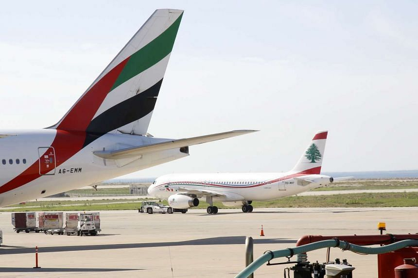 Planes from Emirates Airlines (left) and Middle East Airlines are seen on the tarmac at Rafik Hariri international airport in the Lebanese capital, Beirut, on Nov 21, 2015.