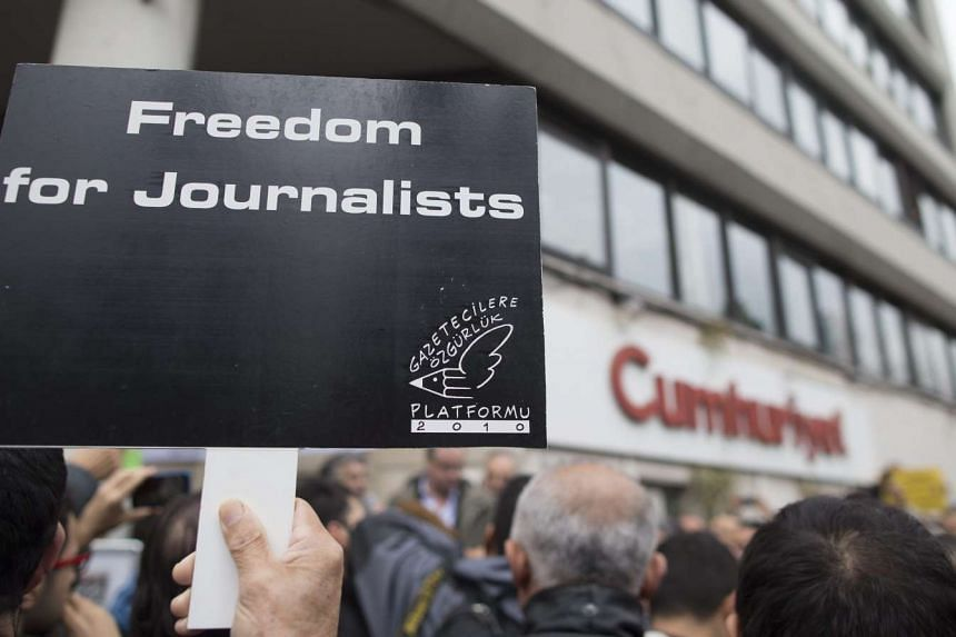 A demonstrator holds a placard reading 'Freedom for journalists' as a group of people gathers in front of the Turkish newspaper 'Cumhuriyet' publishing house, in support of journalists Can Dundar and Erdem Gul who were arrested by an Istanbul court,