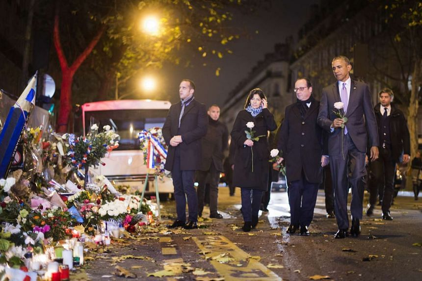 US President Barack Obama (right) paying his respects with French counterpart Francois Hollande at a memorial outside the Bataclan theatre in Paris.